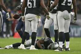 Oakland Raiders wide receiver Amari Cooper (89) lays on the field after getting injured during the first half of an NFL football game against Seattle Seahawks at Wembley stadium in London, Sunday, Oct. 14, 2018. (AP Photo/Tim Ireland)