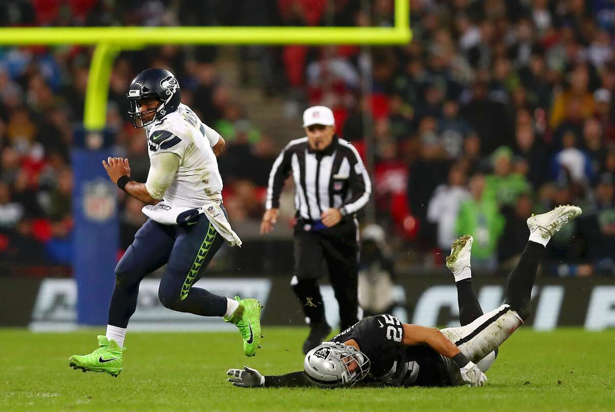 LONDON, ENGLAND - OCTOBER 14: Russell Wilson of Seattle Seahawks is tackled by Erik Harris of Oakland Raiders during the NFL International series match between Seattle Seahawks and Oakland Raiders at Wembley Stadium on October 14, 2018 in London, England. (Photo by Naomi Baker/Getty Images)