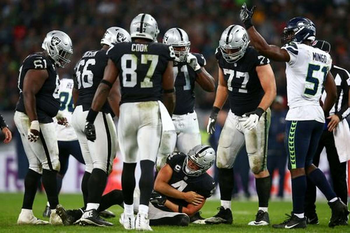 LONDON, ENGLAND - OCTOBER 14: Derek Carr #4 of the Oakland Raiders holds his arm as he lies injured in the ground after taking a hit during the NFL International Series game between Seattle Seahawks and Oakland Raiders at Wembley Stadium on October 14, 2018 in London, England. (Photo by Dan Istitene/Getty Images)