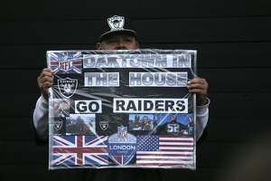 An Oakland Raiders supporter poses for a photo on Wembley Way before an NFL football game against Seattle Seahawks at Wembley stadium in London, Sunday, Oct. 14, 2018. (AP Photo/Tim Ireland)