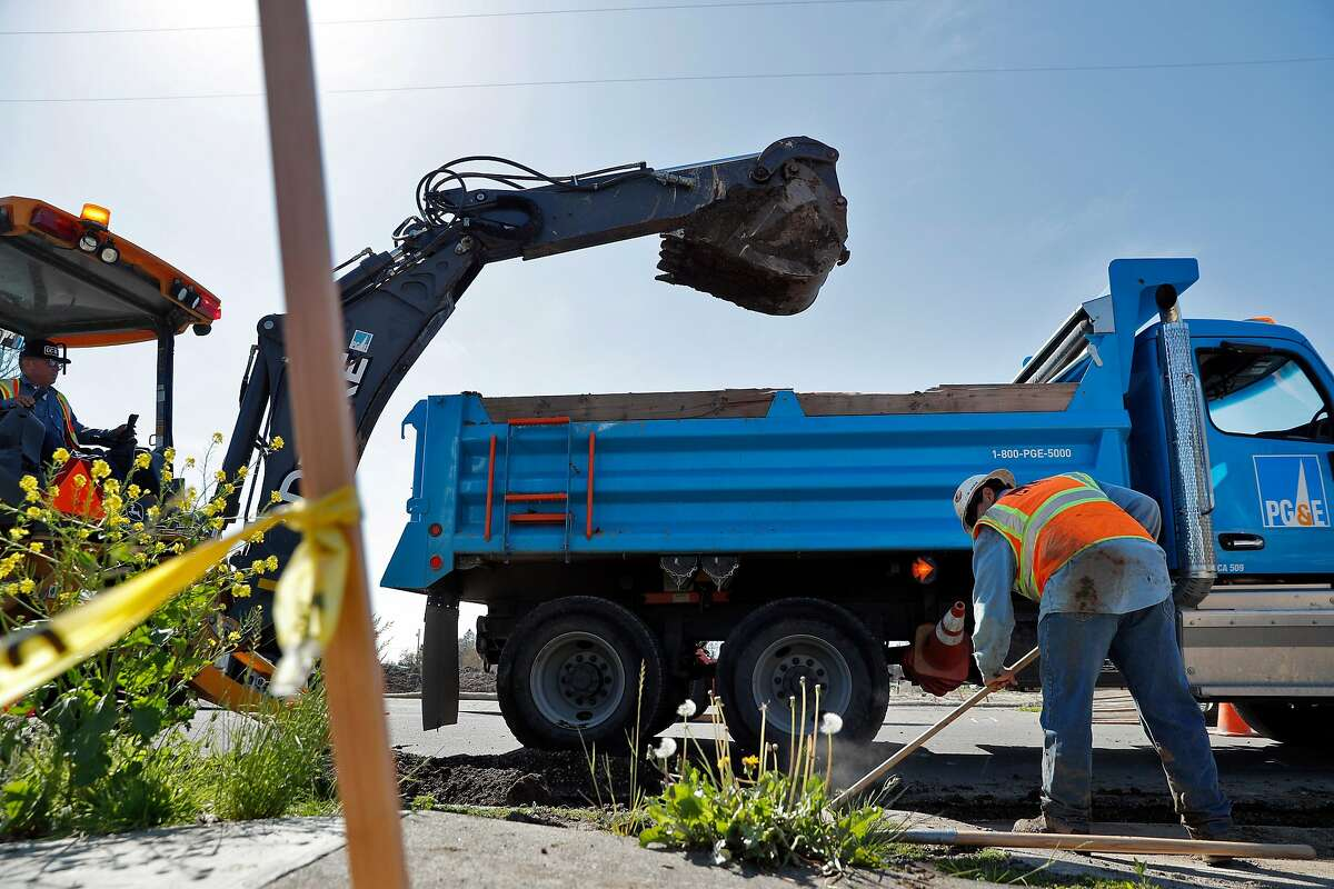 A PG&E worker moves spilled dirt as a trencher digs a trench as PG&E crews and subcontractors began prepping for underground utility lines in the Coffey Park neighborhood of Santa Rosa, Calif., on Monday, April 2, 2018. The neighborhood was devastated by fire in October as dozens of residents perished when thousands of homes in the region were destroyed in the North Bay fires in the region.