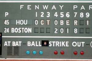 Boston Red Sox scoreboard operators stand in openings on the scoreboard on the Green Monster before Game 2 of the American League Championship Series against the Houston Astros at Fenway Park on Sunday, Oct. 14, 2018, in Boston.