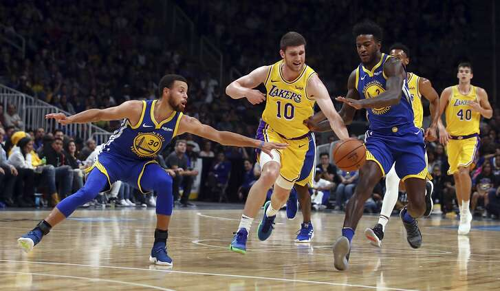 Los Angeles Lakers' Sviatoslav Mykhailiuk (10) drives the ball between Golden State Warriors' Stephen Curry, left, and Jordan Bell (2) during the first half of a preseason NBA basketball game Friday, Oct. 12, 2018, in San Jose, Calif. (AP Photo/Ben Margot)