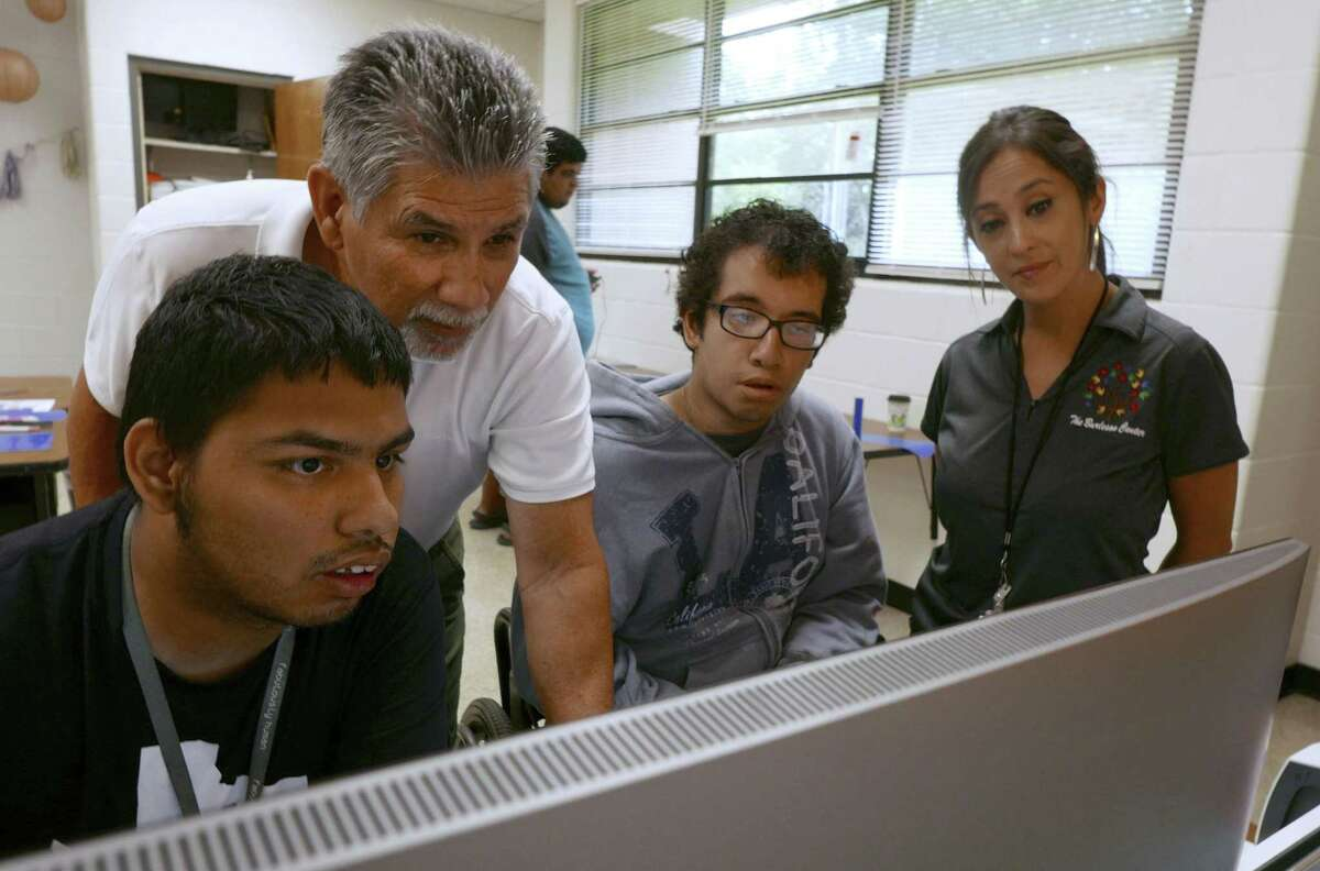 Special education teacher Ric Castillo, second from left, helps students Justin Avila, left, and Marcos Cazares as they work on a T-shirt logo in the print shop at the Burleson Center for Education and Innovation on Oct. 11, 2018. Job coach Julie Garza is at right.