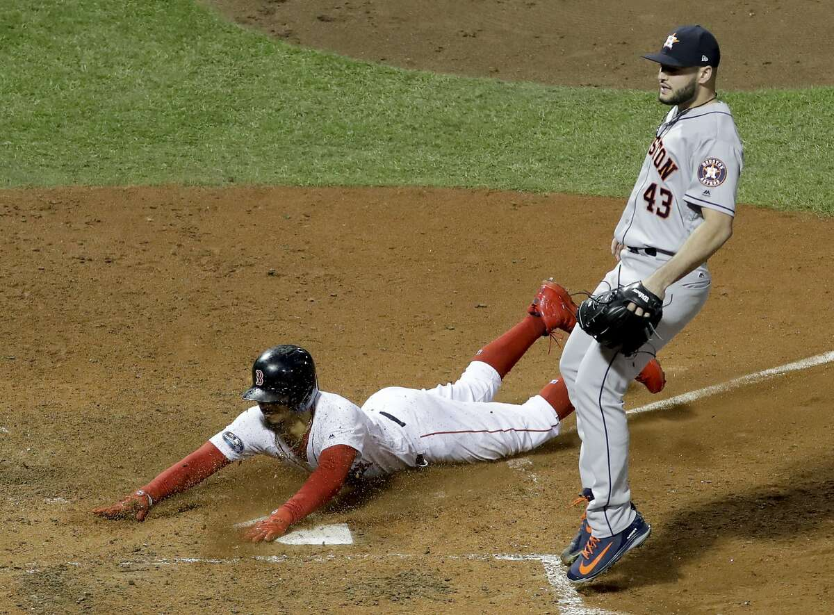 Boston Red Sox's Mookie Betts scores by Houston Astros pitcher Lance McCullers Jr. on a passed ball during the seventh inning in Game 2 of a baseball American League Championship Series on Sunday, Oct. 14, 2018, in Boston. (AP Photo/David J. Phillip)