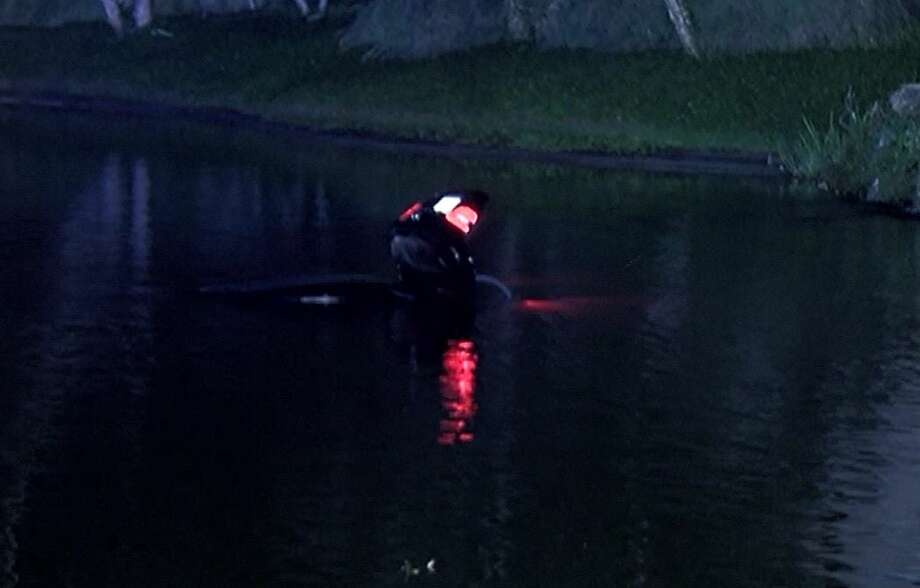 A 4-door car carrying three drove off the road and into a pond Sunday in Montgomery County. Photo: Scott Engle / Montgomery County Police Reporter