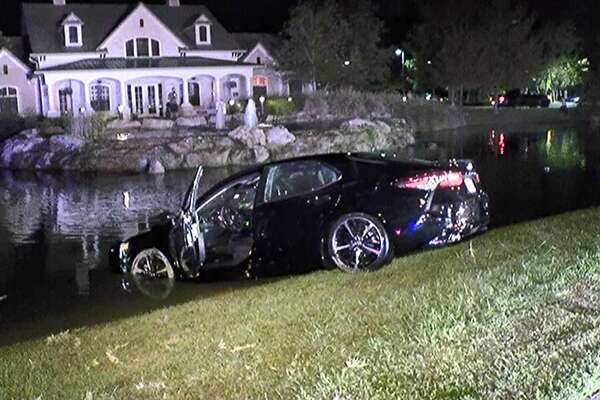A 4-door sedan is pulled from a pond Sunday northeast of Spring in Montgomery County.