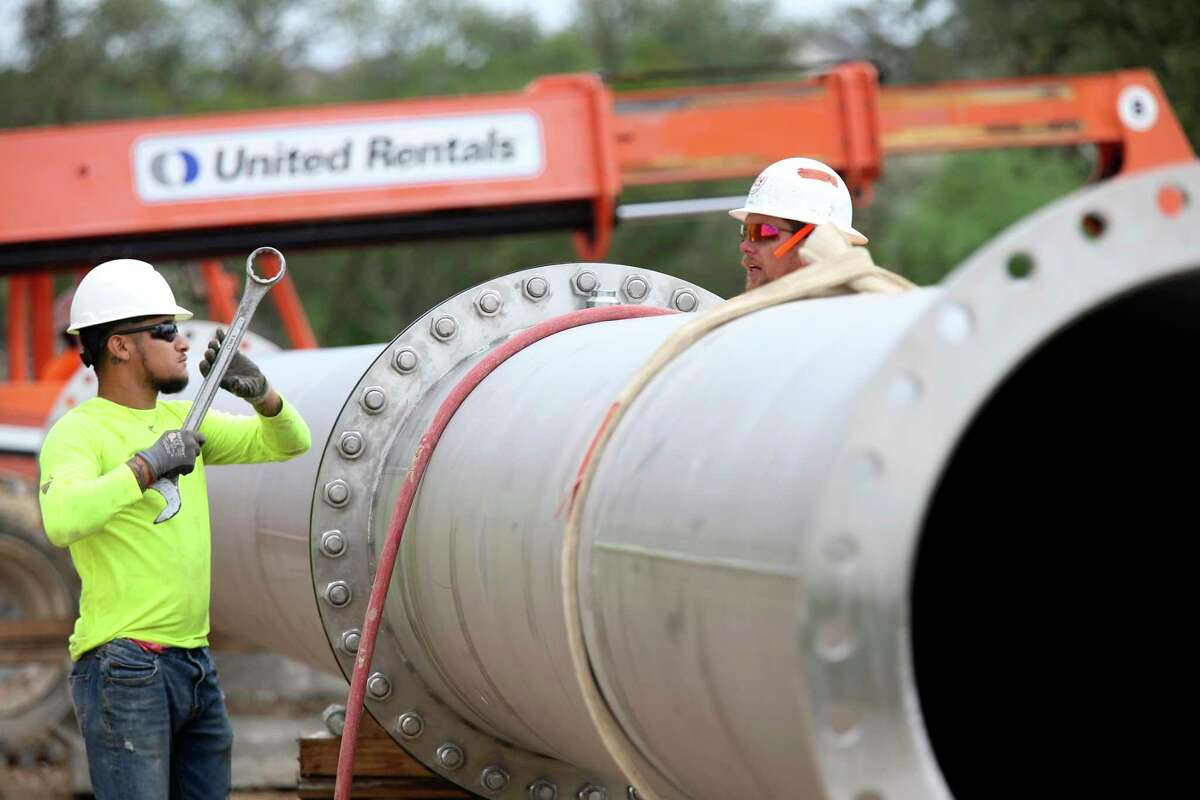 Ishmael Martinez, left, and John Grimes work on an outlet pipe at the Agua Vista Station in the Stone Oak area in October 2018. The 80-foot-tall tank is designed to hold 10 million gallons of water from the Vista Ridge pipeline, running from Burleson County to San Antonio. The station has two tanks and can treat 45 million gallons of water a day. The tanks are each made of 47 wall panels and 80 dome panels.