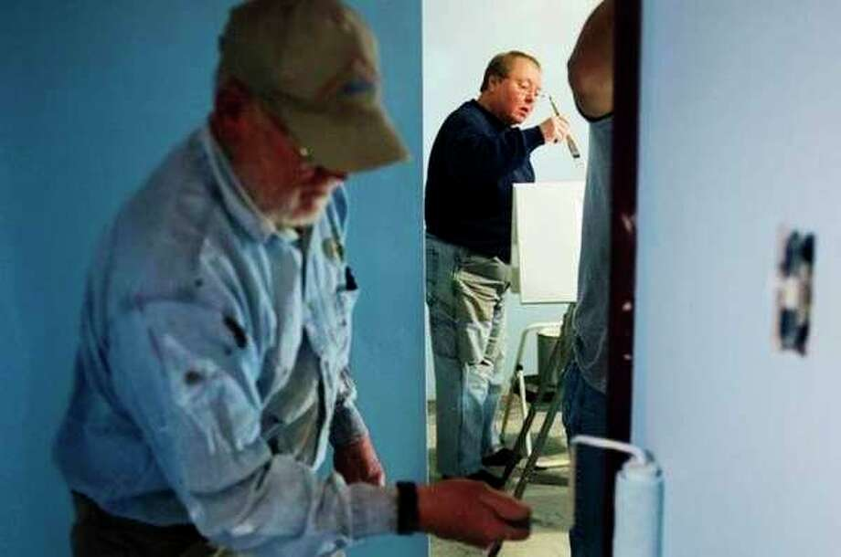 Midland residents Betsy Evans, center, and Eldon Enger, left, work to paint the walls of a bedroom on April 18. Volunteers from Trinity Lutheran worked over a two-week period to repair three Midland homes from damage sustained in the historic June 2017 flooding. (Daily News File Photo)