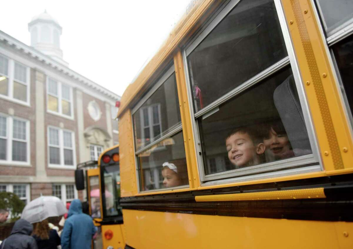 First-graders look out the window of their bus bound for Old Greenwich School.