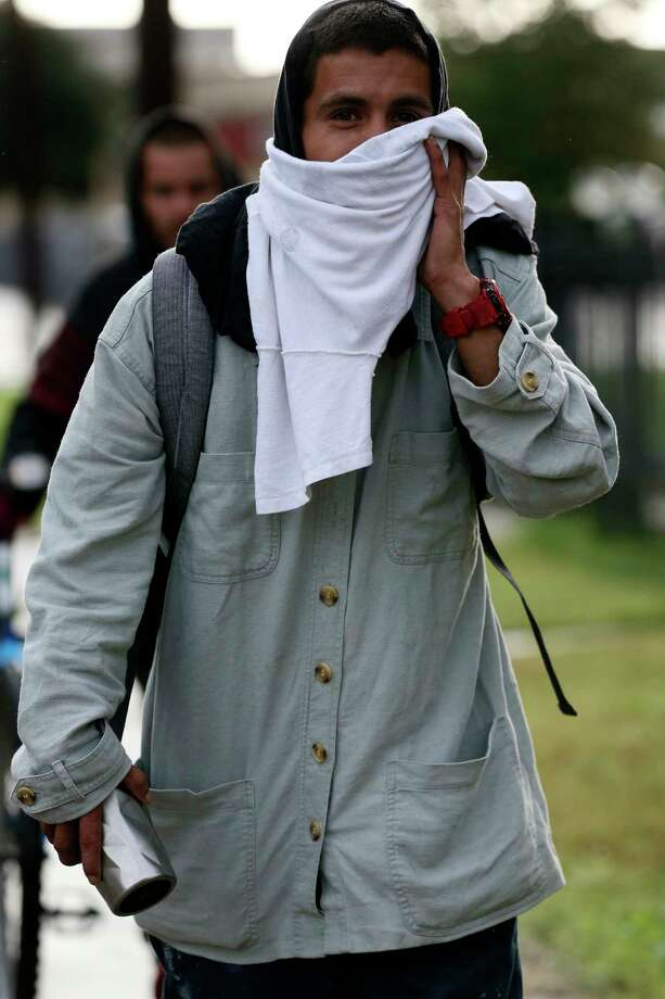 Anthony Aguilar, 26, covers up while walking on Dakota Street, Monday, Oct. 15, 2018. A cold front blows into the San Antonio area bringing rains and temperatures in the mid-40's for the first time this year. According the National Weather Service, the area is expected to receive 1 to 2 inches of rain. Photo: JERRY LARA, San Antonio Express-News / © 2018 San Antonio Express-News