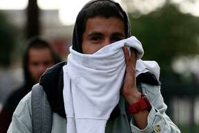Anthony Aguilar, 26, covers up while walking on Dakota Street, Monday, Oct. 15, 2018. A cold front blows into the San Antonio area bringing rains and temperatures in the mid-40's for the first time this year. According the National Weather Service, the area is expected to receive 1 to 2 inches of rain.