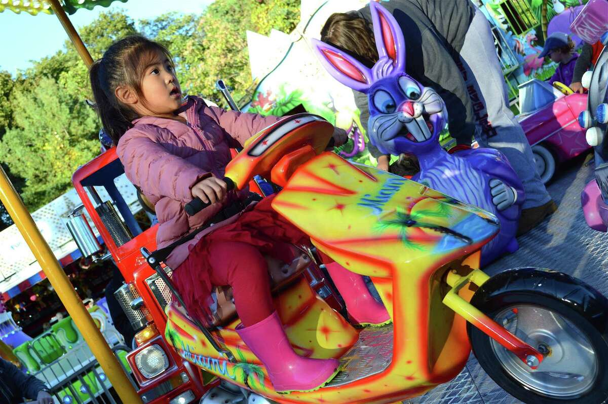 Abigail Kim, 4, of New Canaan, revs up for a ride at the New Canaan Nature Center's Fall Fair, Friday evening, Oct. 12, 2018, in New Canaan, Conn.