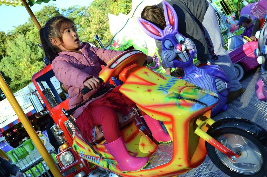 Abigail Kim, 4, of New Canaan, revs up for a ride at the New Canaan Nature Center's Fall Fair, Friday evening, Oct. 12, 2018, in New Canaan, Conn. Photo: Jarret Liotta / For Hearst Connecticut Media / New Canaan News Freelance