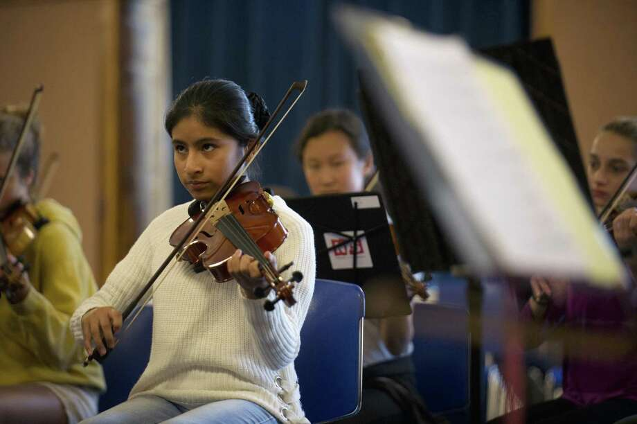 Emily Huyhua, 14, of Stamford, plays the violin during a Norwalk Youth Symphony rehearsal inside Norwalk City Hall on Sunday. Huyhua successfully auditioned for the symphony through a community engagement partnership with Stamford-based music education nonprofit INTEMPO. Photo: Michael Cummo / Hearst Connecticut Media / Stamford Advocate
