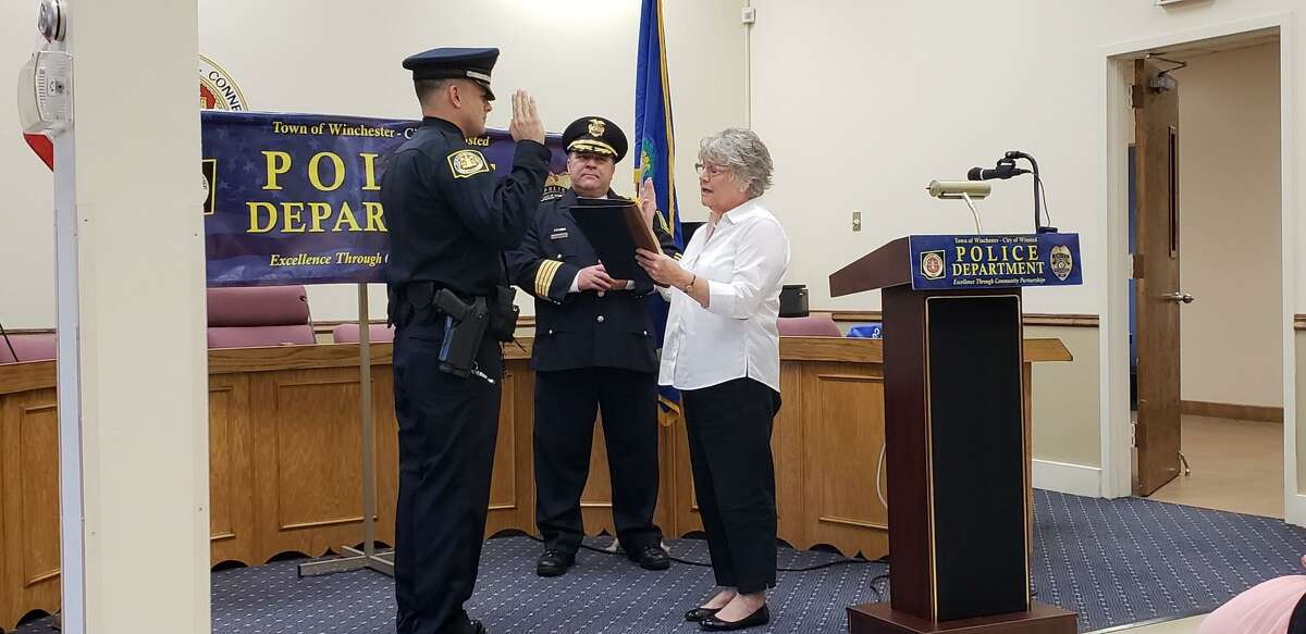 Town Clerk Sheila Sedlak swears in a new Winchester police officer.