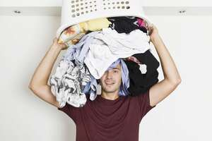 Frustrated young man with full of clothes on his head. Laundry time
