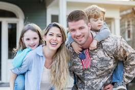 Happy mid adult soldier returns home from overseas assignment. He is holding his preschool age son. His wife is standing beside him. She is holding their daughter.