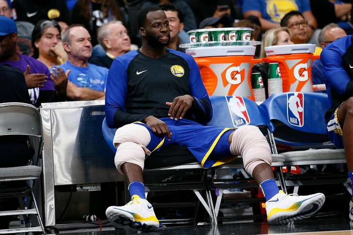 Golden State Warriors forward Draymond Green (23) on the bench with his knees wrapped with ice during the second half of an NBA preseason game at SAP Center on Friday, Oct. 12, 2018, in San Jose, Calif.