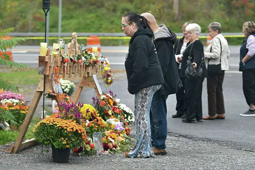 People visit a growing memorial for the Schoharie limo crash victims at the site of the accident next to the Apple Barrel Store on Monday, Oct. 15, 2018 in Schoharie, N.Y. (Lori Van Buren/Times Union)