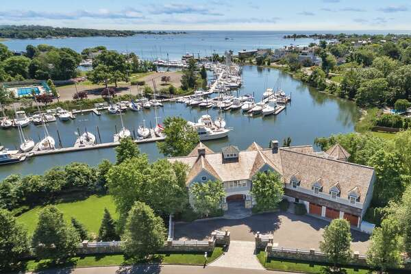 The 7,478-square-foot gray shingle contemporary colonial at 15 Duck Pond Road sits on a level property of three quarters of an acre comprising 270 feet of direct waterfront.