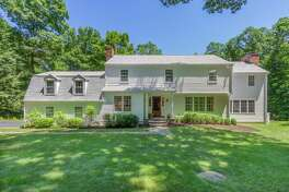 The white colonial house at 79 Scarlet Oak Drive enjoys a wealth of privacy on its secluded, tree-lined two-acre property abutting Kellogg Drive Open Space.