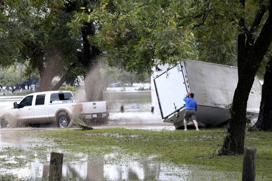 People try to upright a trailer on the grounds of the Kimble County River Park in Junction, Texas, Monday, Oct. 8, 2018. Heavy rains the area caused the Llano River to flood and about 19 people were rescued. One woman swept away by floodwaters drifted approximately 25 miles before she was rescued, according to the Texas A&M Forest Service. Photo: JERRY LARA/San Antonio Express-News