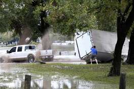 People try to upright a trailer on the grounds of the Kimble County River Park in Junction, Texas, Monday, Oct. 8, 2018. Heavy rains the area caused the Llano River to flood and about 19 people were rescued. One woman swept away by floodwaters drifted approximately 25 miles before she was rescued, according to the Texas A&M Forest Service.