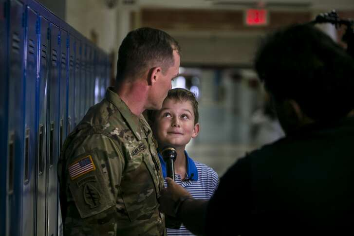 Kaden Hawkins, 13, looks up at his dad Army Special Forces Medical Sgt. Shan Hawkins as they are interviewed at Stevenson Middle School after Sgt. Hawkins surprised Kaden in his pre-AP algebra class Friday, Oct. 12, 2018.