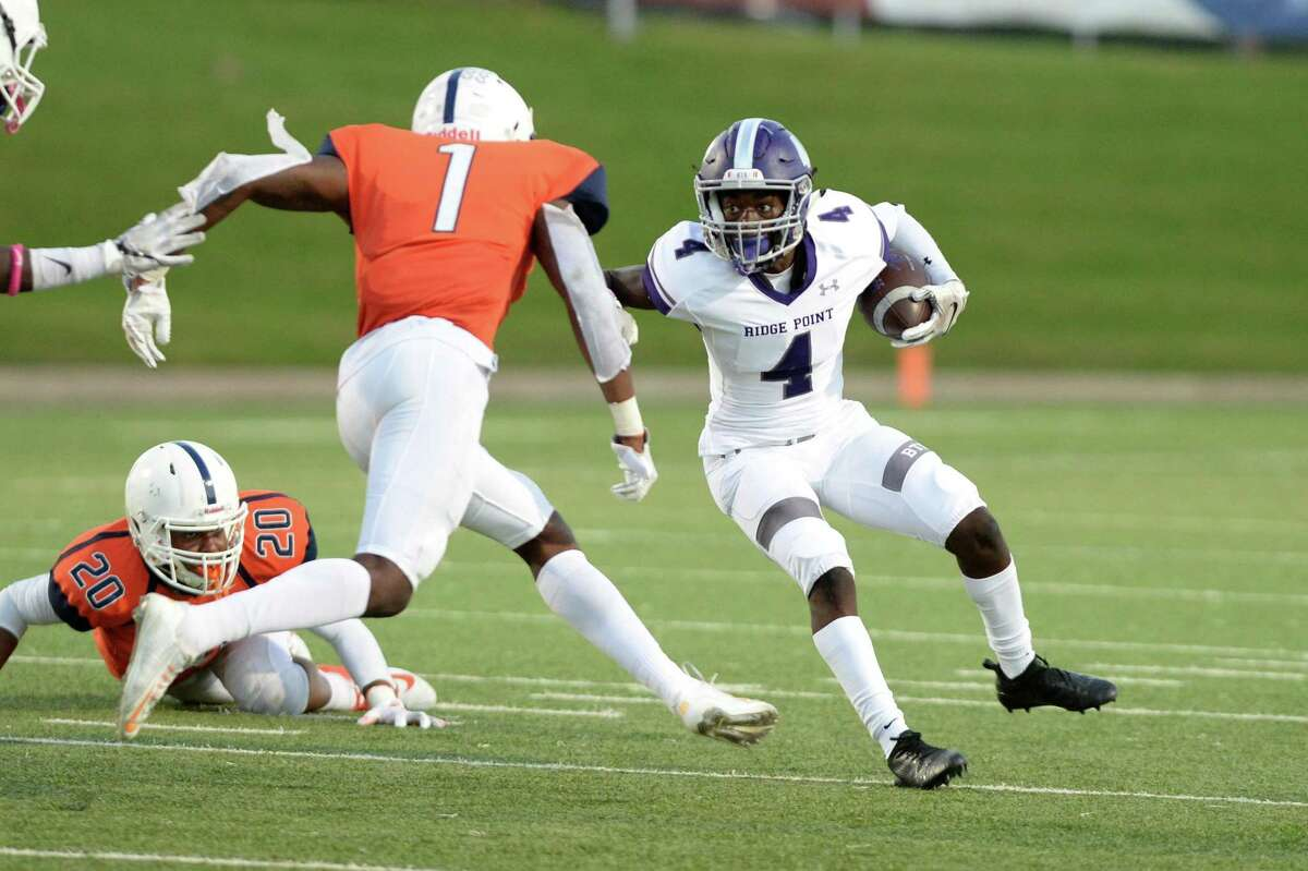Keenon Pitts (4) of Ridge Point tries to avoid a tackle by Jamal Morris (1) of Bush in the second quarter of a high school football game between the Bush Broncos and the Ridge Point Panthers on Saturday, October 13, 2018 at Mercer Stadium, Sugar Land, TX.