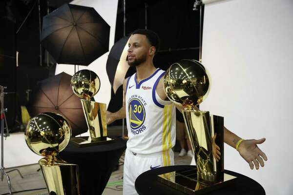 OAKLAND, CA - SEPTEMBER 24: Stephen Curry #30 of the Golden State Warriors poses with three Larry O'Brien NBA Championship Trophies during the Golden State Warriors media day on September 24, 2018 in Oakland, California.