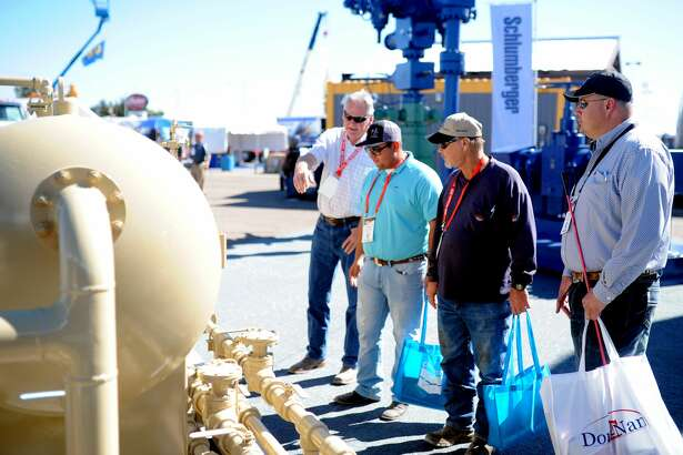 Attendees at the 2016 Permian Basin International Oil Show view equipment on display at the Schlumberger booth.