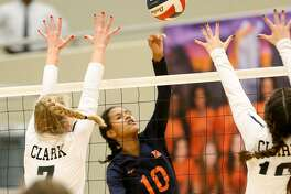Brandeis' Maya Smalls (center) hits the ball between Clark's Shadee Briggs (left) and Micayla Reiland during their District 28-6A high school volleyball match at Taylor Fieldhouse on Tuesday, Oct. 2, 2018. Clark won the match in five sets.