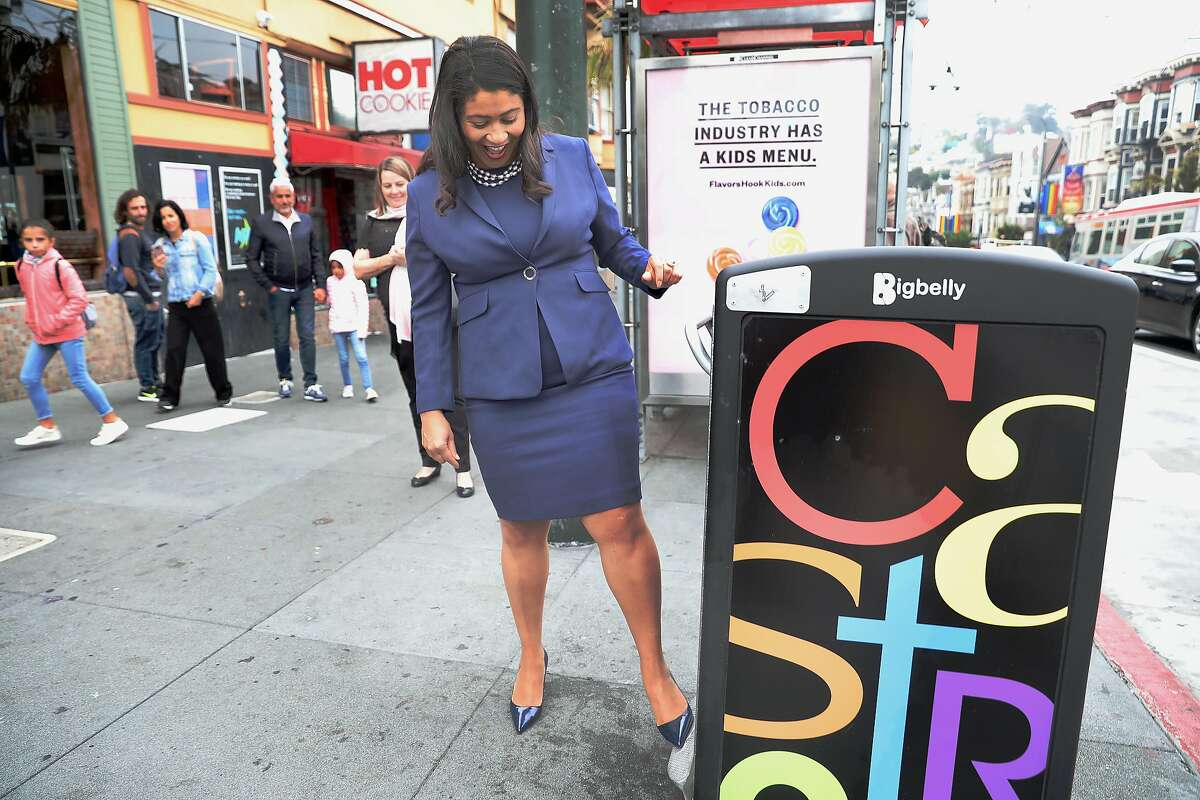 SF Mayor London Breed tries a feature of the new big belly garbage can while she takes a neighborhood walk this morning around the Castro on Monday, Aug. 13, 2018 in San Francisco, Calif.