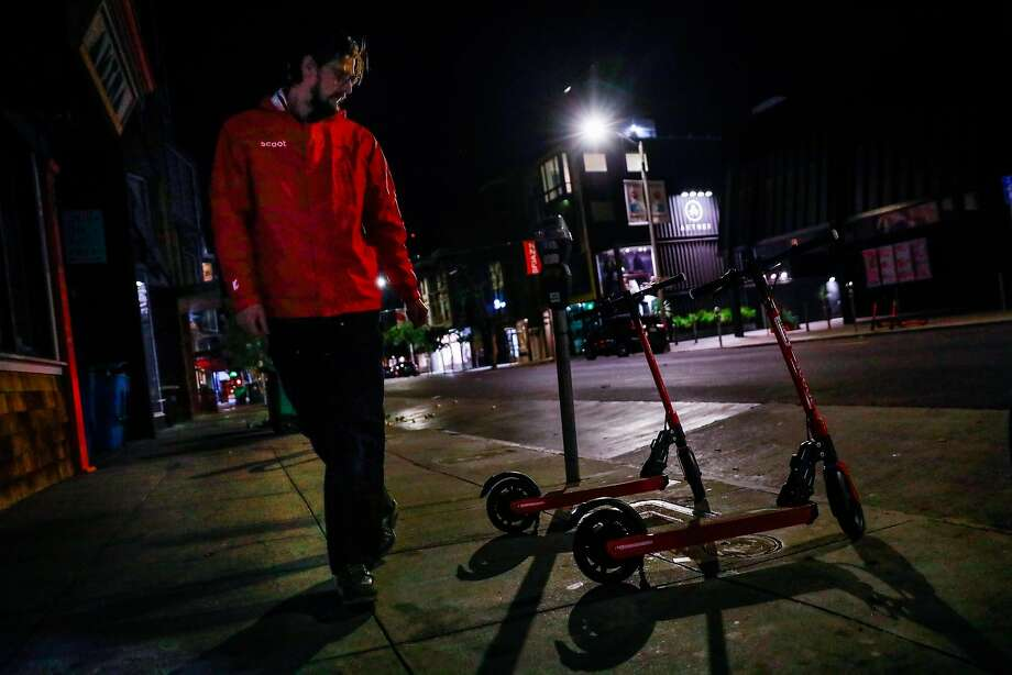 Scoot fleet manager Matt Roth unloads electric scooters in Hayes Valley on Monday as the vehicles zip back into S.F. Photo: Gabrielle Lurie / The Chronicle
