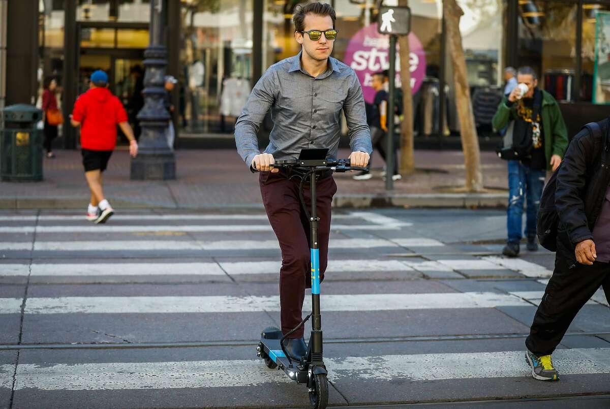 Jordan Rejaud rides a Skip scooter across Market Street in San Francisco, California, on Monday, Oct. 15, 2018.