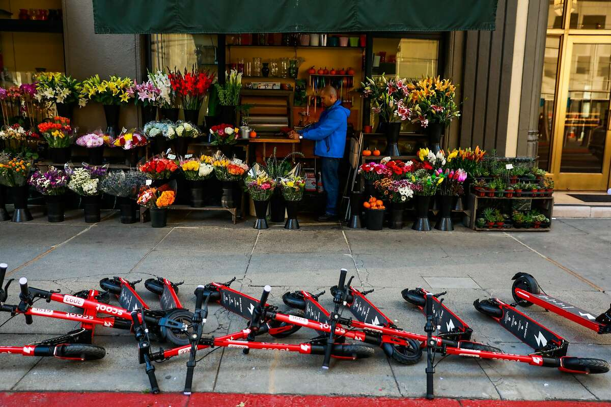 Scoot scooters that have been knocked over lay on the sidewalk on Mission and 1st Streets in San Francisco, California, on Monday, Oct. 15, 2018.