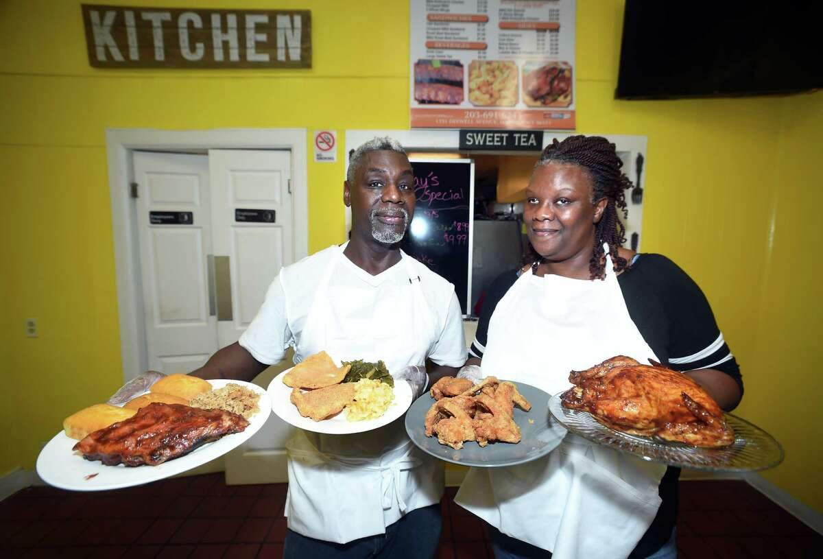 Darryl Pervis (left) and his wife, Thomea Oliver Pervis, show off some of the selections available at their store, DPERV'S T.O.P. BBQ on Dixwell Ave. in Hamden on October 15, 2018. Darryl is holding a plate of baby back ribs, chopped pork bbq and cornbread (left) and another with fried swai fish, macaroni and cheese and collard greens. Thomea is holding a plate of fried chicken wings and another with a whole rotisserie bbq chicken.