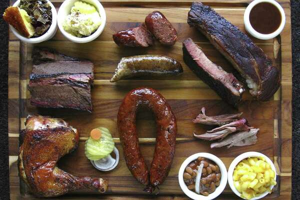 Barbecue and sides from Ed's Smok-N-Q. Clockwise from top left: cornbread, collard greens, potato salad, Yoakum link sausage, pork spare ribs, barbecue sauce, pulled pork, mac and cheese, baked beans, Schulenburg ring sausage, chicken, brisket and Port Arthur boudin sausage.
