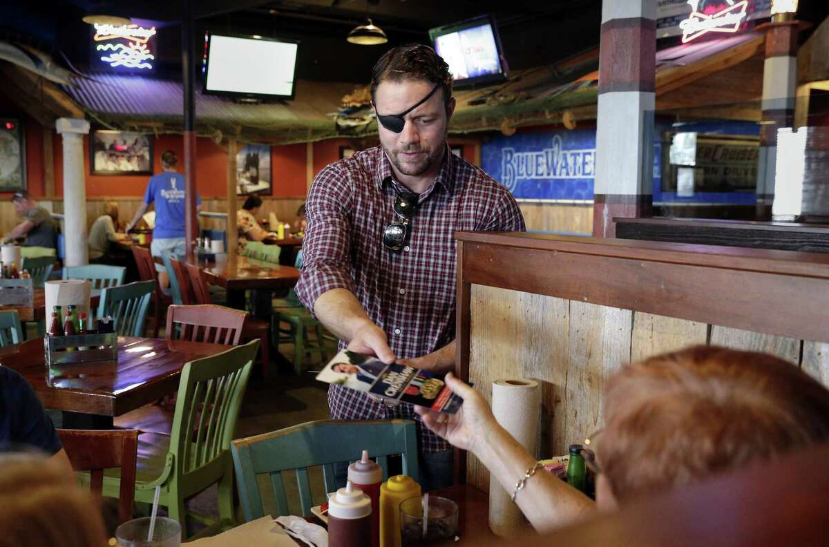 Dan Crenshaw, candidate for the 2nd congressional district, hands out campaign literature to customers at the Spring's Bluewater Seafood Restaurant in September. Crenshaw was at the restaurant to help collect donated items for Hurricane Florence victims.