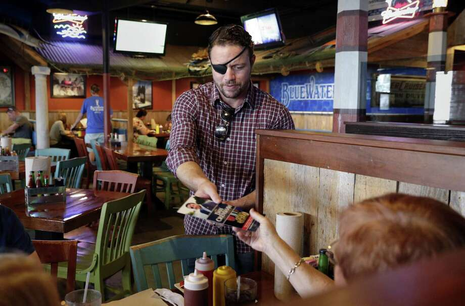 Dan Crenshaw, candidate for the 2nd congressional district, hands out campaign literature to customers at the Spring's Bluewater Seafood Restaurant in September. Crenshaw was at the restaurant to help collect donated items for Hurricane Florence victims. Photo: Michael Wyke, Houston Chronicle / Contributor / © 2018 Houston Chronicle