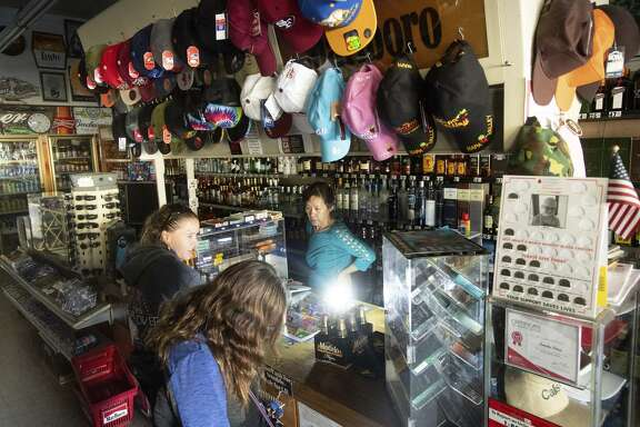 Victoria Um serves customers in the dark at the Calistoga Smoke Shop on Monday. Residents' routines and tourists' plans were upended when PG&E shut down power to Calistoga and other towns Sunday.