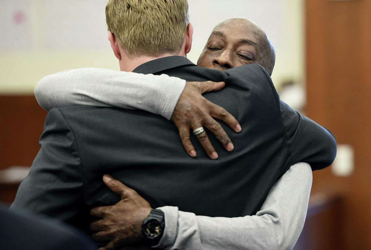Plaintiff Dewayne Johnson, facing camera, hugs one of his lawyers after hearing the verdict in his case against Monsanto at the Superior Court of California in San Francisco on Friday, Aug. 10, 2018. A San Francisco jury on Friday ordered agribusiness giant Monsanto to pay $289 million to the former school groundskeeper dying of cancer, saying the company's popular Roundup weed killer contributed to his disease.
