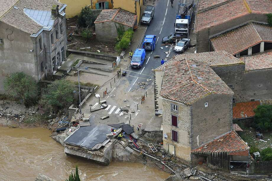 TOPSHOT - An aerial view shows a collapsed bridge in the city of Villegailhenc, near Carcassonne, southern France, on October 15, 2018, following heavy rains that saw rivers bursting banks. - At least 13 people died as violent rainstorms turned rivers into raging torrents in southwestern France on October 15 in the latest episode of wild weather in Europe, officials said. Flash floods swamped a number of towns and villages around the fortress city of Carcassonne, leaving a trail of overturned cars, damaged roads and collapsed homes (Photo by SYLVAIN THOMAS / AFP)SYLVAIN THOMAS/AFP/Getty Images Photo: SYLVAIN THOMAS, AFP/Getty Images