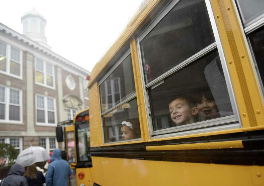 First-grader Joseph Prisinzano looks out the window of his bus bound for Old Greenwich School on students' first day back at Cos Cob School in the Cos Cob section of Greenwich, Conn. Monday, Oct. 15, 2018. Students didn't attend school last week as officials assessed the flood damage to Cos Cob School. Classes resumed at the school Monday for third- through fifth-graders while kindergarteners were sent to Parkway School and first- and second-graders sent to Old Greenwich School. Officials estimate the damage at $2 million and hope to be finished with repairs by winter break in December. Photo: Tyler Sizemore / Hearst Connecticut Media / Greenwich Time