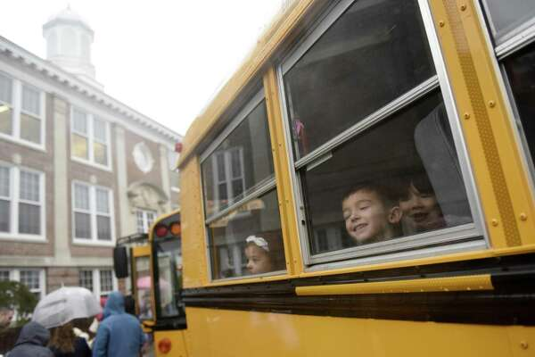 First-grader Joseph Prisinzano looks out the window of his bus bound for Old Greenwich School on students' first day back at Cos Cob School in the Cos Cob section of Greenwich, Conn. Monday, Oct. 15, 2018. Students didn't attend school last week as officials assessed the flood damage to Cos Cob School. Classes resumed at the school Monday for third- through fifth-graders while kindergarteners were sent to Parkway School and first- and second-graders sent to Old Greenwich School. Officials estimate the damage at $2 million and hope to be finished with repairs by winter break in December.