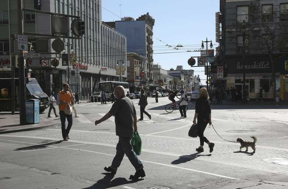 Pedestrians cross on Sixth Street at Market Street, where officials have proposed widening sidewalks at the expense of a traffic lane to accommodate pedestrian safety. The Municipal Transportation Agency will vote on whether to remove a southbound auto lane on Sixth. Photo: Liz Hafalia / The Chronicle / online_yes
