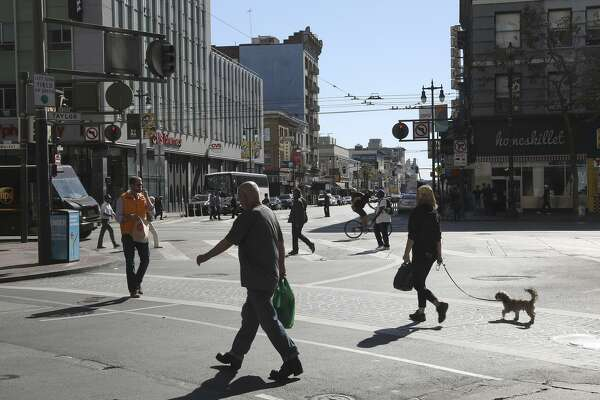 Pedestrians cross on Sixth Street at Market Street, where officials have proposed widening sidewalks at the expense of a traffic lane to accommodate pedestrian safety. The Municipal Transportation Agency will vote on whether to remove a southbound auto lane on Sixth.