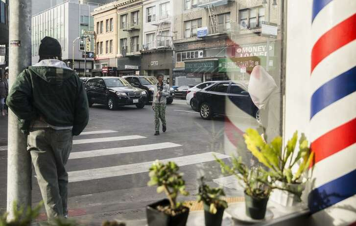 People walk through backed-up traffic lanes on Sixth Street, where business interests object to losing a driving lane.