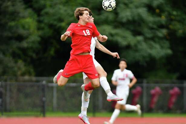 Greenwich's Daniel Bourgeois (18) leaps in the air to challenge for a loose ball during Monday's game against Warde.